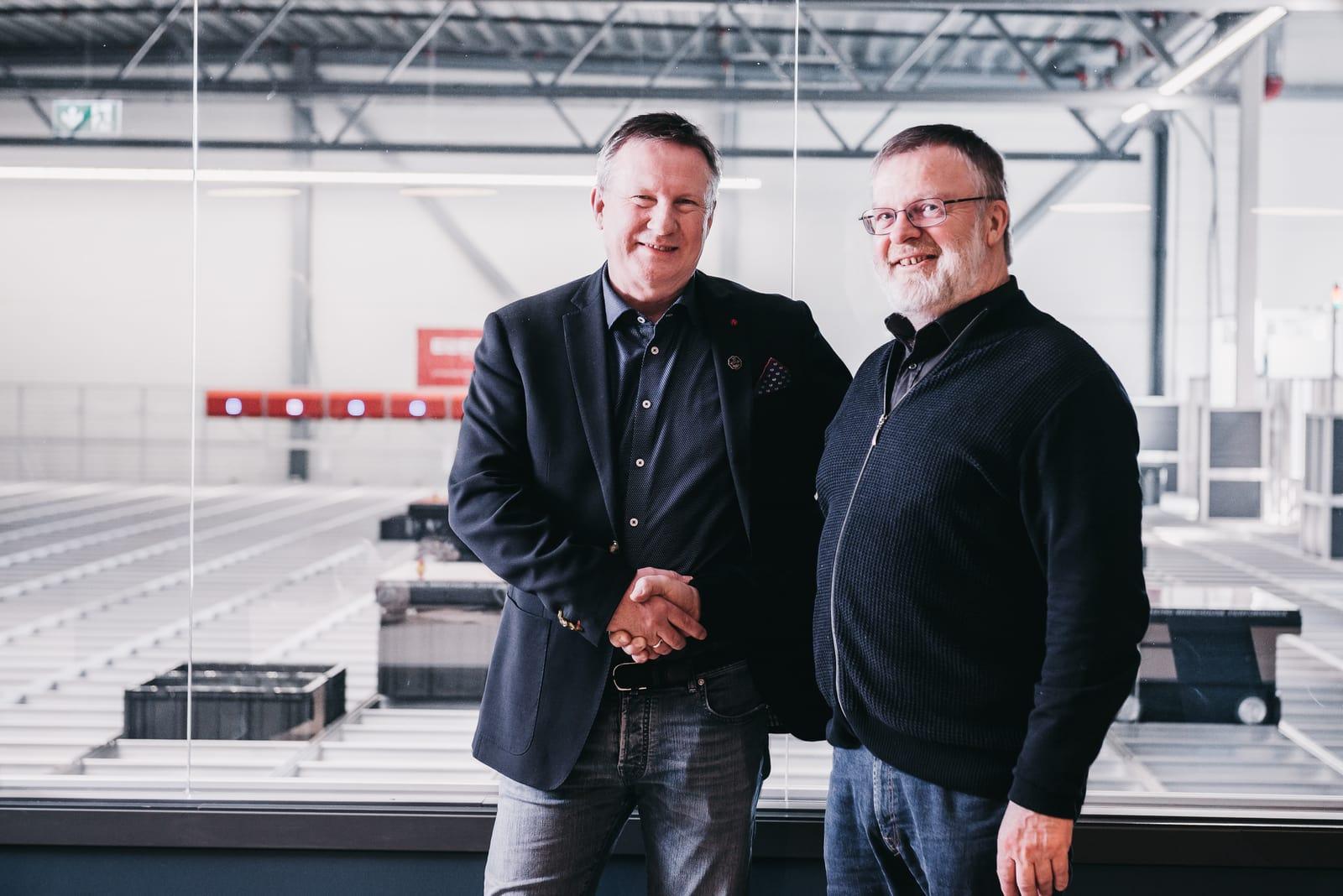 Morten Halvorsen og Kjell Blakseth håndhilser foran robotlageret til New Wave