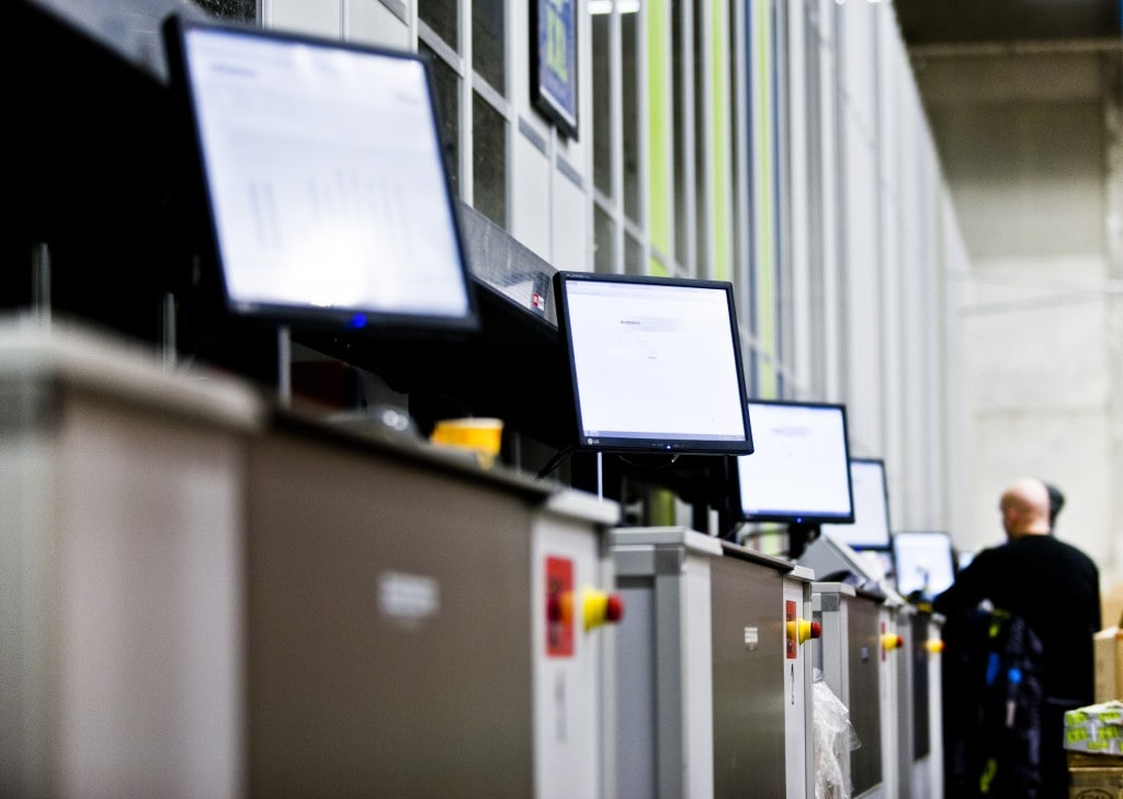 Dataskjermer ved plukkstasjonene på lageret til XXL